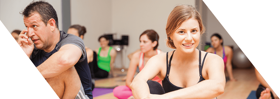 Women smiling, sat on mats in group exercise class