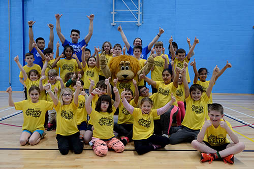 Junior sports camp group photo with arms above head