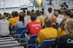 Volunteers sit amongst spectators in the Arena bleacher seats overlooking the squash courts for World Uni Squash
