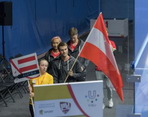 Emily holds an Austria placard in a line of volunteers and players walking into the World Uni Squash Opening Ceremony