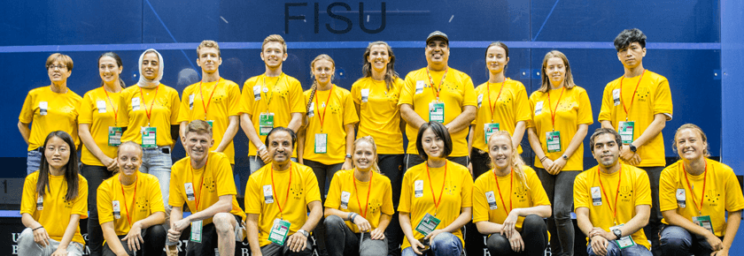 Squash volunteers line up with their accreditation and yellow volunteer t-shirts inside of glass court at World Uni Squash Championships 2018