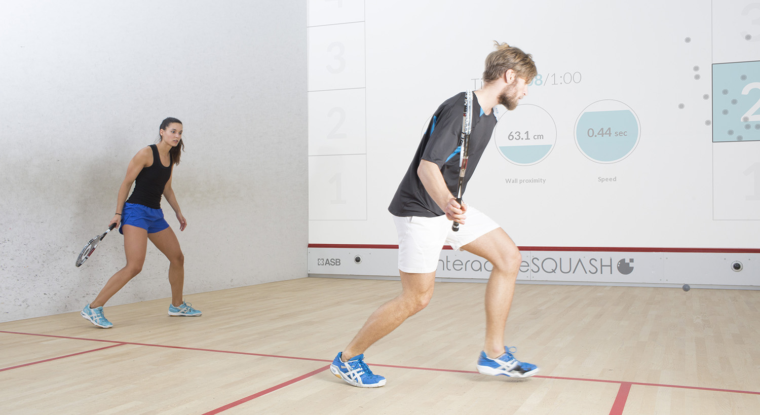 Male and female playing interactiveSQUASH