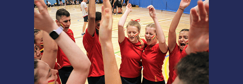 Korfball team huddle in a circle at half-time, putting their hands in and cheering