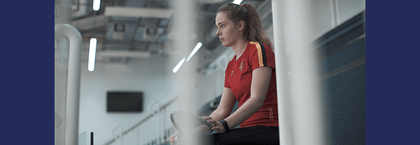 Squash player Kiera Marshall sits in stands overlooking squash courts with her racket