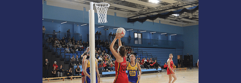 UoB netballer lines up shot underneath post with crowd watching from bleacher seating
