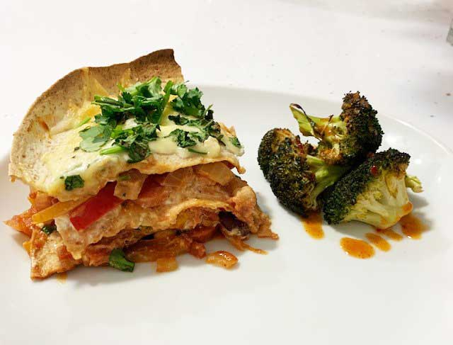 Enchilada pie with side of broccoli on white plate