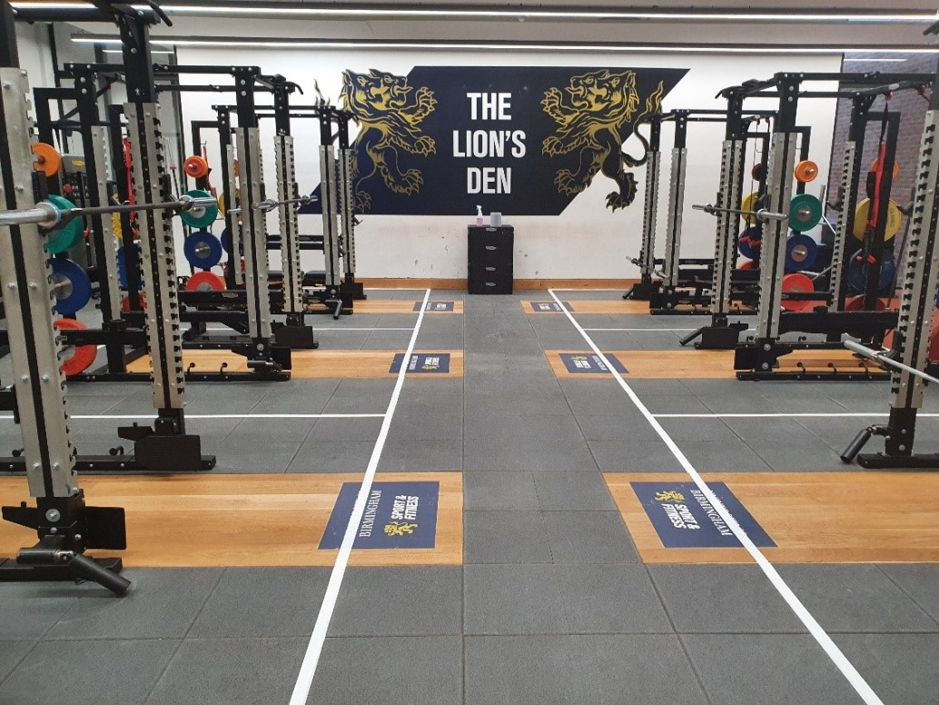 """The performance gym with squat racks, and a graphic on the wall quoting """"the lions den"""""""