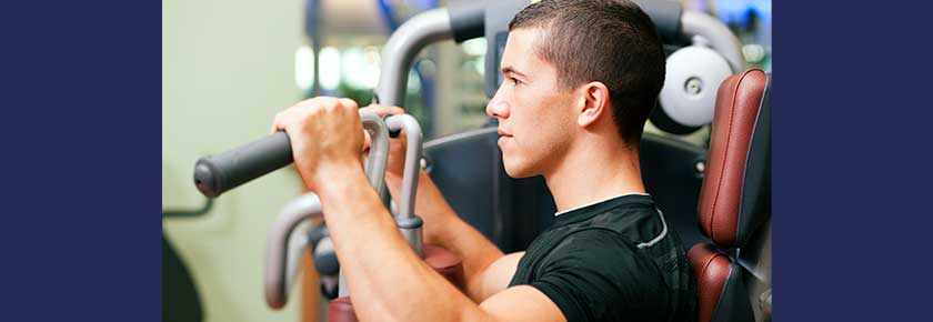 Man working out in gym on machine